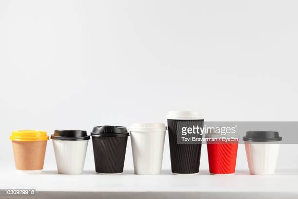 Close-Up Of Disposable Coffee Cups Over White Background