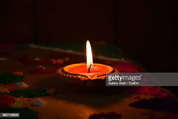 close-up of diya on floor in darkroom - diya oil lamp stock pictures, royalty-free photos & images