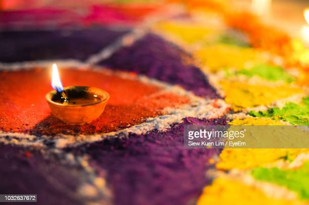 Close-Up Of Diya On Rangoli