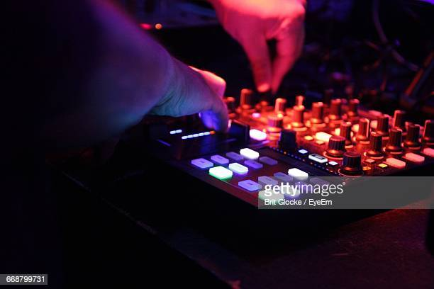 Close-Up Of Dj Adjusting Knobs On Sound Mixer