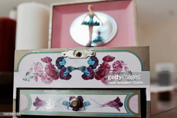 Close-Up Of Doll On Music Box At Table
