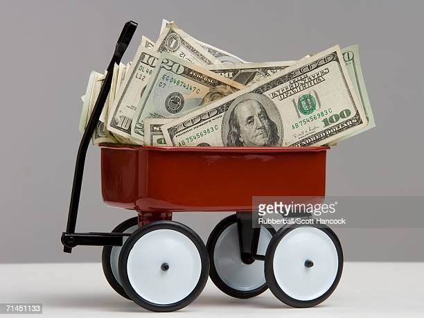 close-up of dollar bills in a toy wagon - toy wagon stock photos and pictures