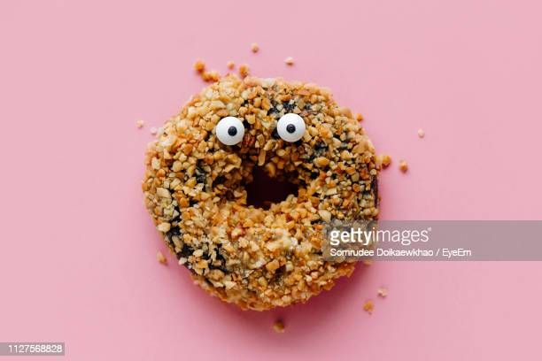 close-up of donut with anthropomorphic face over pink background - anthropomorphic face stock pictures, royalty-free photos & images