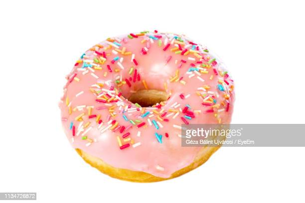 close-up of donut with colorful sprinkles on white background - ドーナツ ストックフォトと画像