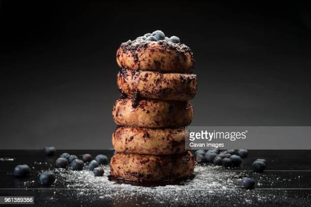 Close-up of donuts with blueberries and powdered sugar on table
