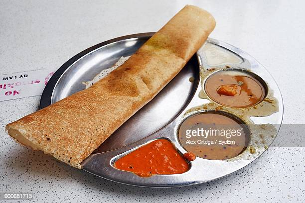 close-up of dosa served in plate on table - dosa stock photos and pictures