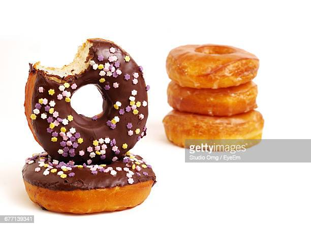 Close-Up Of Doughnuts With Chocolate Icing And Sprinkles Against White Background