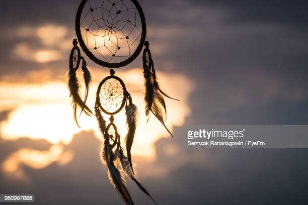 Close-Up Of Dreamcatcher Against Cloudy Sky During Sunset