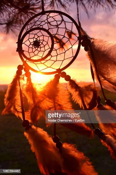 close-up of dreamcatcher against sky during sunset - dreamcatcher stock pictures, royalty-free photos & images