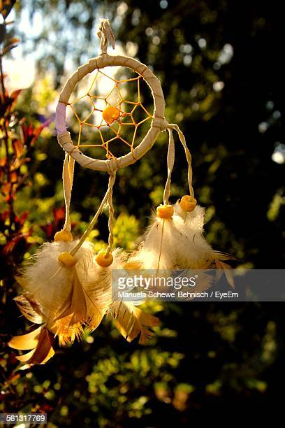 Close-Up Of Dreamcatcher Hanging Against Trees
