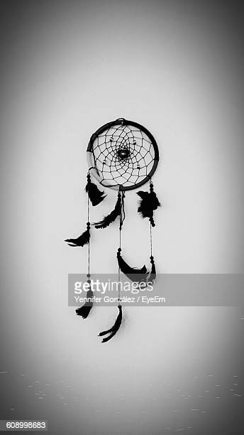 Close-Up Of Dreamcatcher Hanging On White Wall