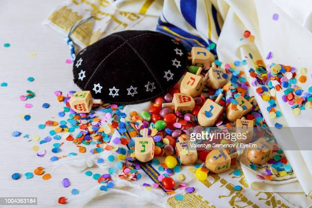 close-up of dreidels with colorful confetti and candies on table - hanukkah stock photos and pictures