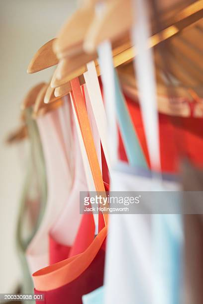 Close-up of dresses hanging by a clothes rack in a clothing store