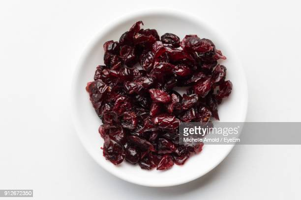 Close-Up Of Dried Cranberries In Plate Over White Background