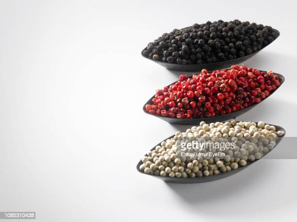 close-up of dried food in bowls over white background - 調味料 ストックフォトと画像
