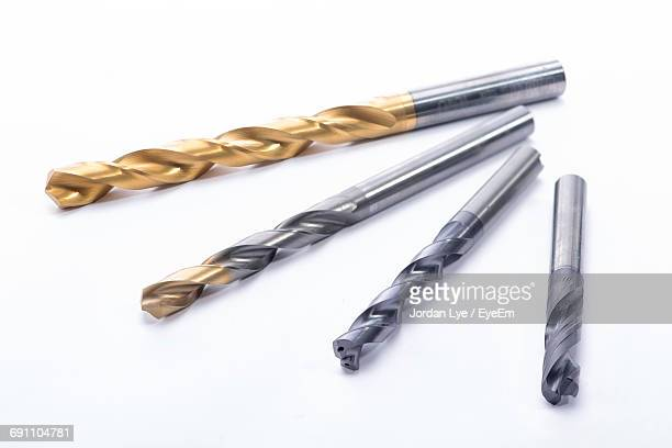 close-up of drill bits arranged on white background - drill bit stock photos and pictures