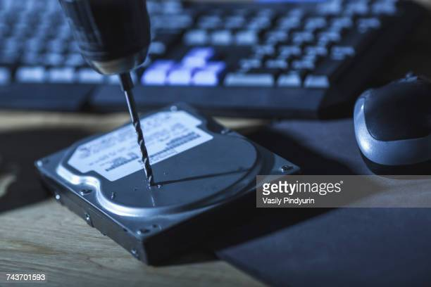 Close-up of drill on hard drive by computer keyboard at table