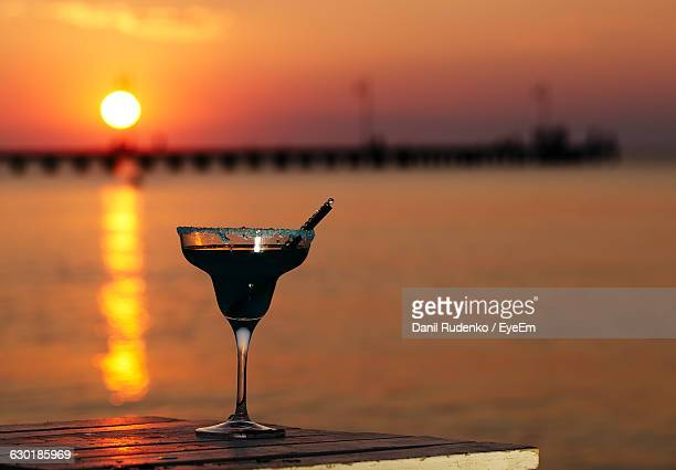 Close-Up Of Drink Against Seascape At Sunset