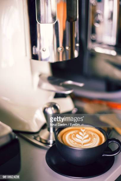close-up of drink by coffee maker on table - coffee drink stock pictures, royalty-free photos & images