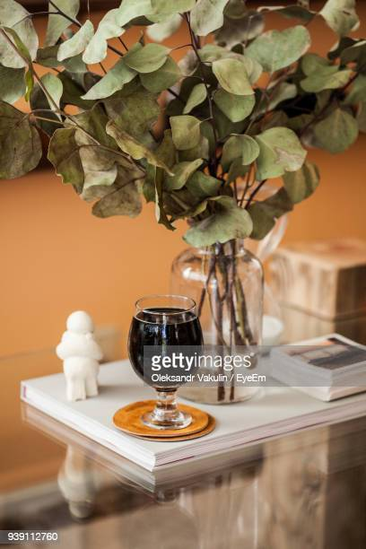 Close-Up Of Drink By Plant On Wooden Table