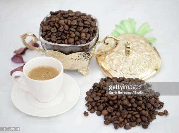 close-up of drink by roasted coffee beans over white background - coffee drink stock pictures, royalty-free photos & images