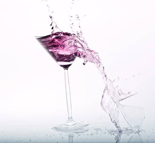 Close-Up Of Drink Falling From Martini Glass Against White Background