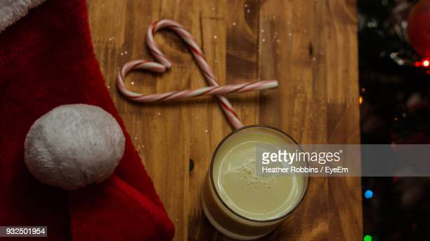 Close-Up Of Drink Glass With Candy Canes And Santa Hat On Table