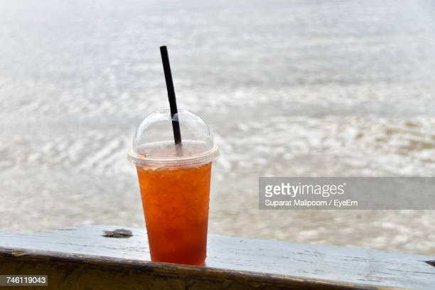 Close-Up Of Drink In Disposable Glass On Wooden Railing By Sea