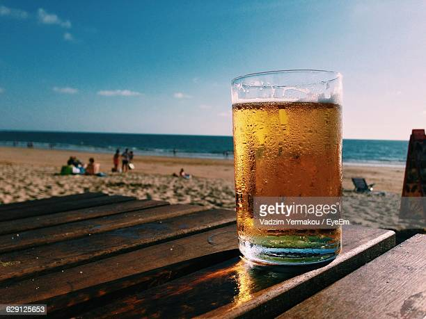 Close-Up Of Drink In Glass On Wooden Table At Beach