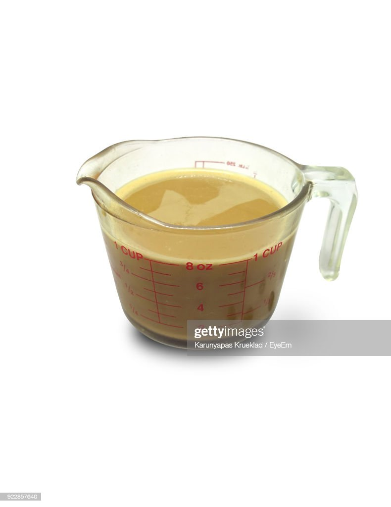 Close-Up Of Drink In Measuring Cup Against White Background : Stock Photo