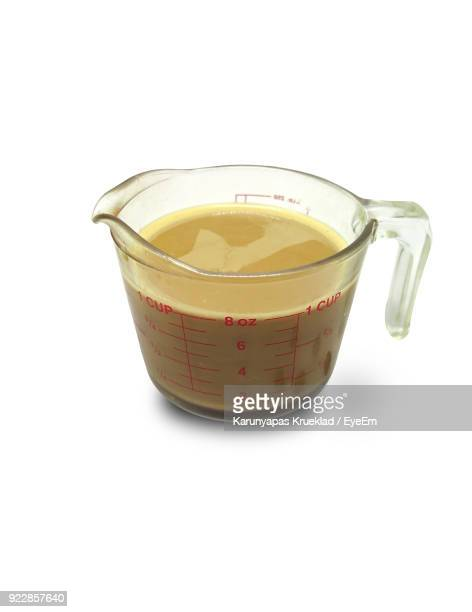 Close-Up Of Drink In Measuring Cup Against White Background
