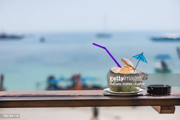 Close-Up Of Drink On Table Against Sea