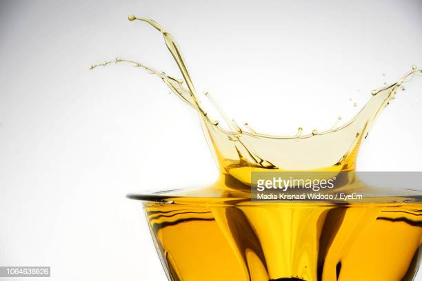 close-up of drink spilling against white background - oil stock pictures, royalty-free photos & images