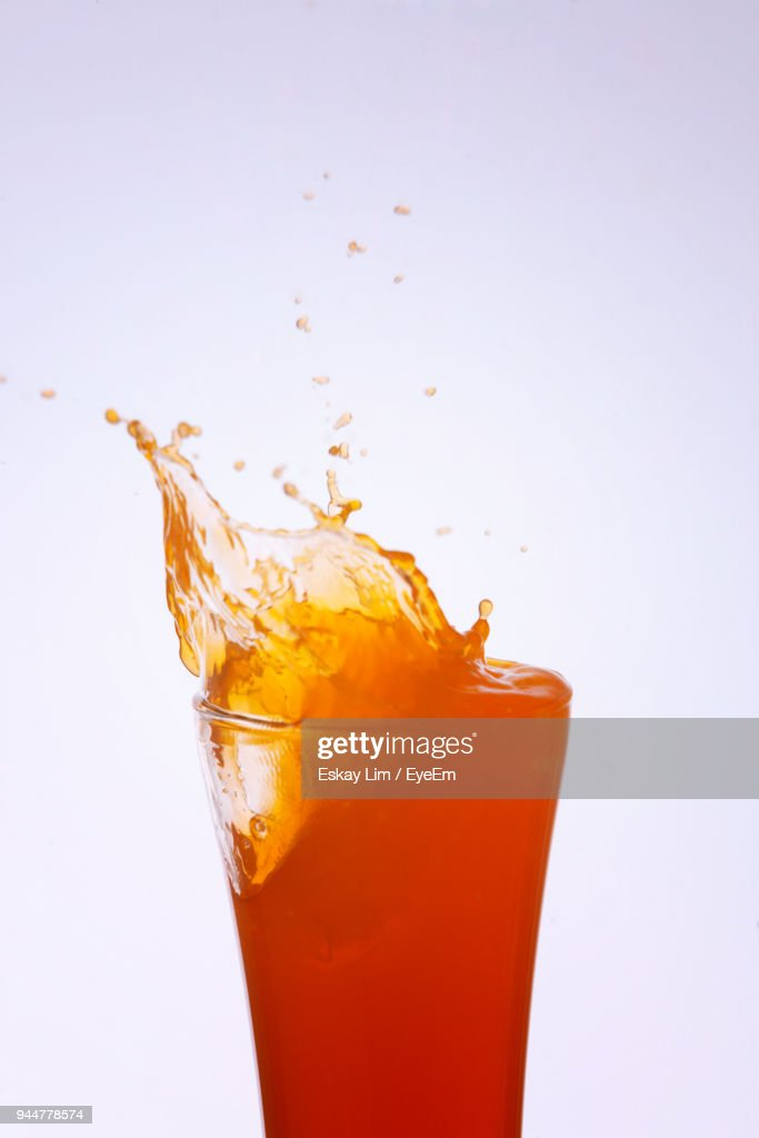 Close-Up Of Drink Splashing From Bottle Over White Background : Stock Photo