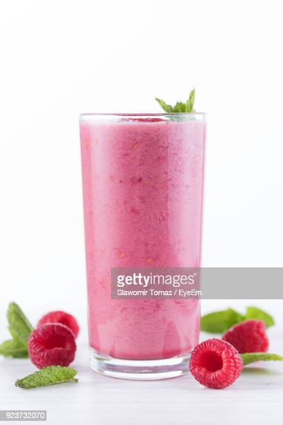 close-up of drink with fruits and herbs on table against white background - milkshake imagens e fotografias de stock