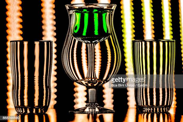 Close-Up Of Drinking Glasses On Table Against Illuminated Lights