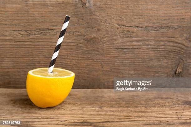 Close-Up Of Drinking Straw In Lemon On Table