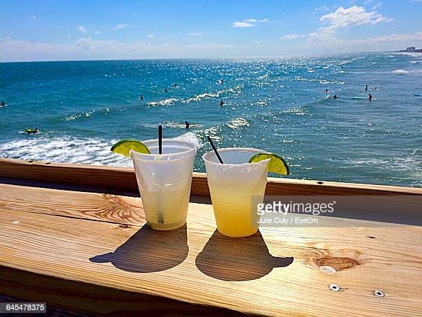 Close-Up Of Drinks Against Calm Sea