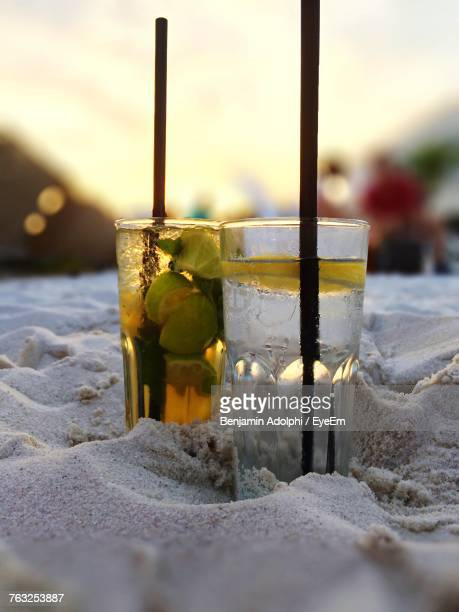 Close-Up Of Drinks On Sand At Beach During Sunset