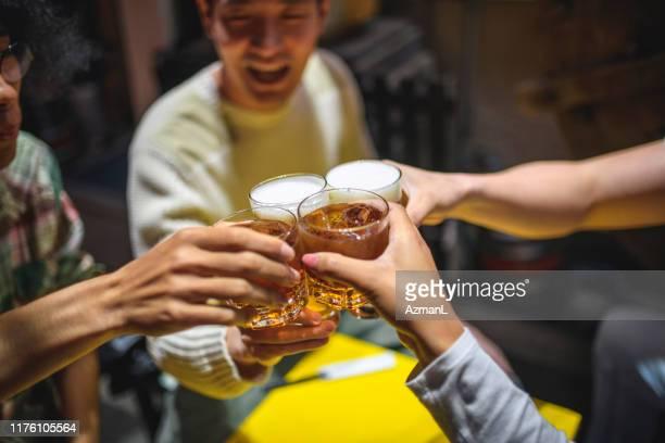 居酒屋でお祝いの乾杯で育てた飲み物のクローズアップ - 飲食店 ストックフォトと画像