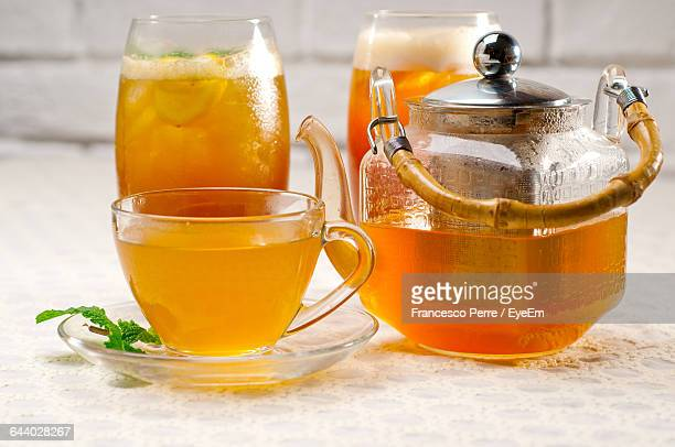 Close-Up Of Drinks With Cup And Teapot On Table