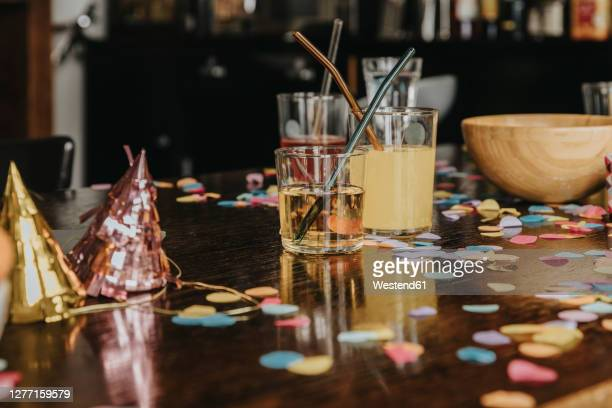 close-up of drinks with party hats and confetti on dining table at home - 宴の後 ストックフォトと画像