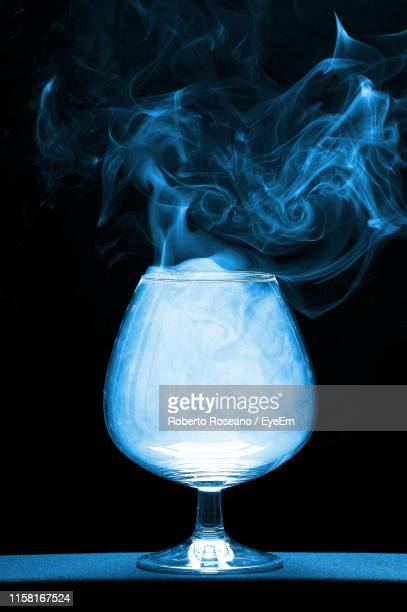 close-up of dry ice in wineglass against black background - dry ice stock pictures, royalty-free photos & images