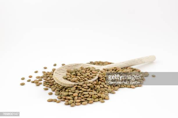 close-up of dry lentils with wooden spoon against white background - lentil stock pictures, royalty-free photos & images