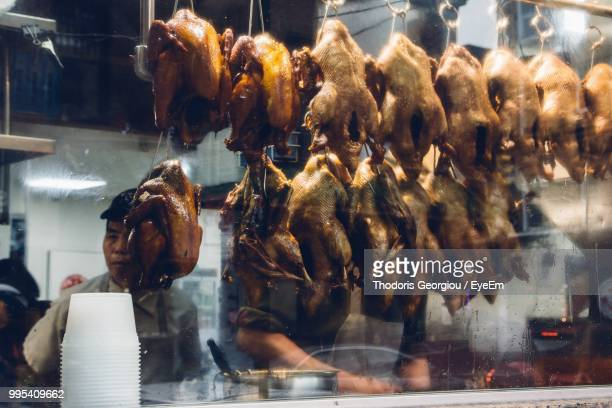 close-up of duck meats hanging at window for sale in store - chinatown stock pictures, royalty-free photos & images