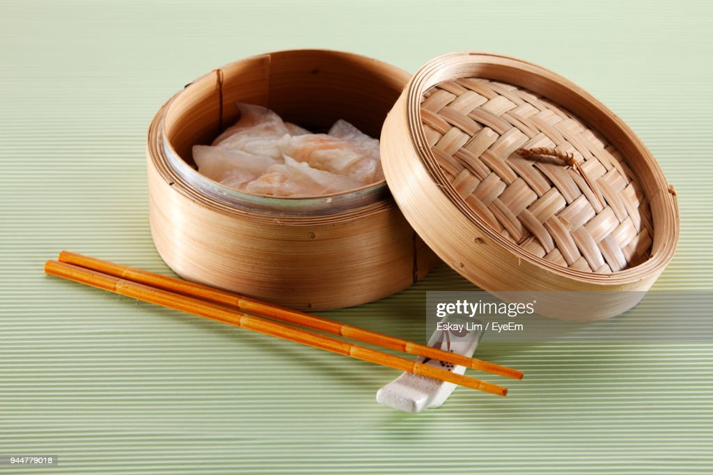 Close-Up Of Dumplings In Container By Chopsticks On Table : Stock Photo