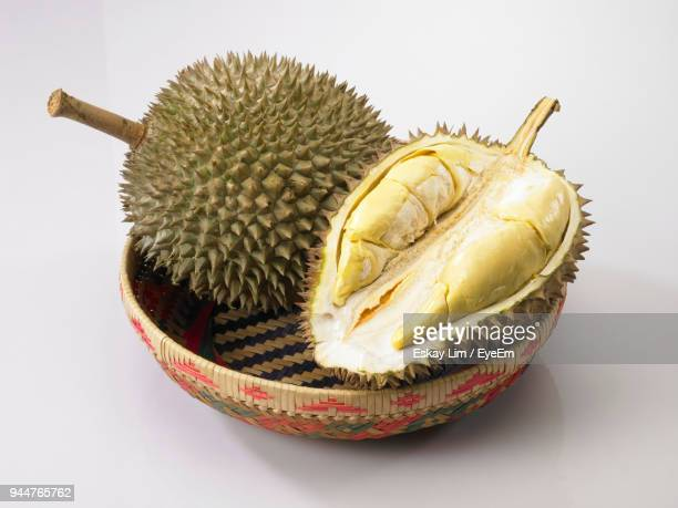 close-up of durian in bowl over white background - durian stock pictures, royalty-free photos & images