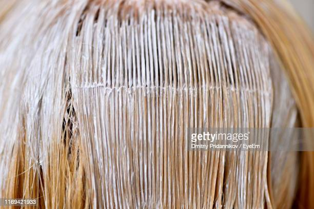 close-up of dye applied on woman hair - dyed hair stock pictures, royalty-free photos & images