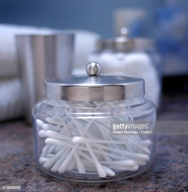 Close-up of ear buds in glass jar