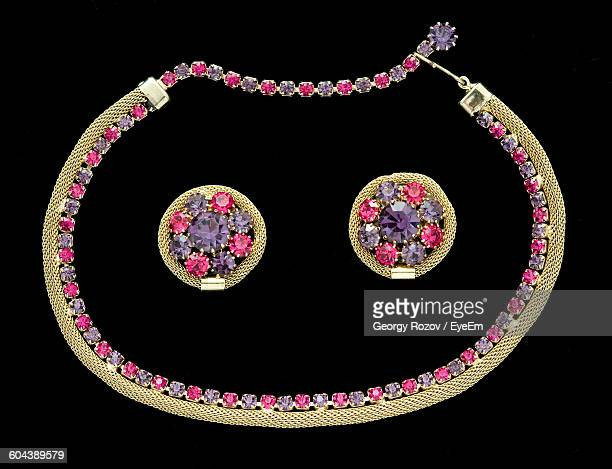 Close-Up Of Earrings And Necklace Over Black Background